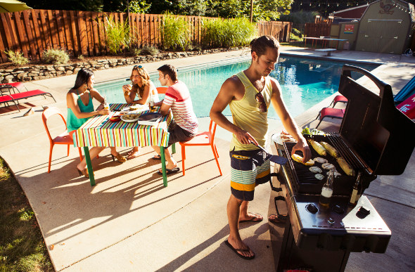 Friends surrounding a BBQ grill with a city backdrop