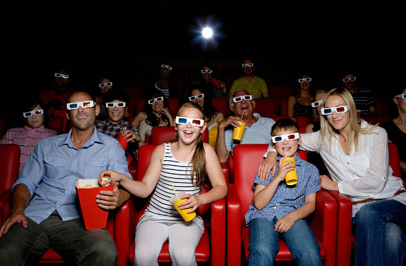 a crowd of people watching a 3D movie at the theatre