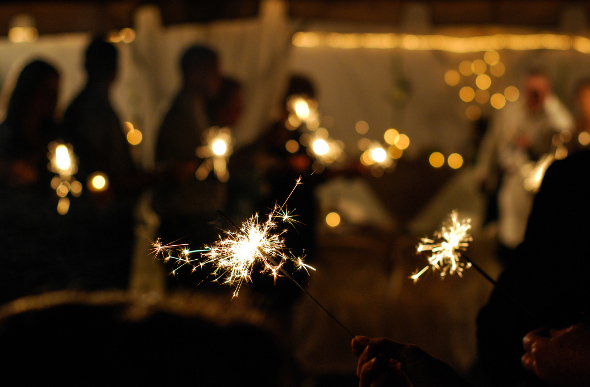 Silhouettes of people holding sparklers
