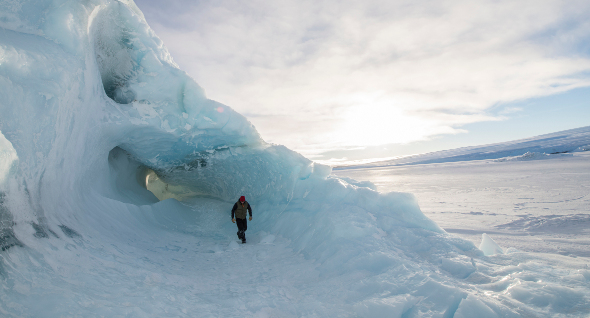An explorer walking on an iceberg
