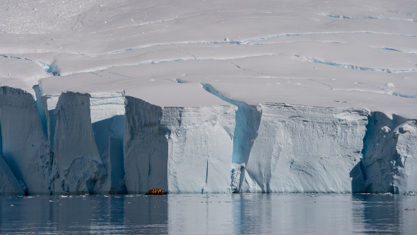 a small explorer boat  infront of a large ice shelf