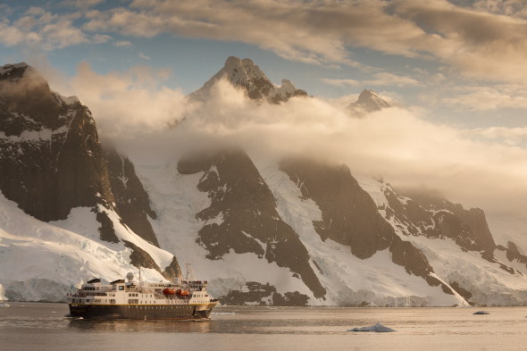 ship cruising infront of snow-capped cliffs