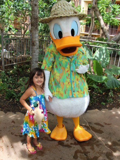 A little girl poses with the Donald Duck character at Aulani, A Disney Resort & Spa