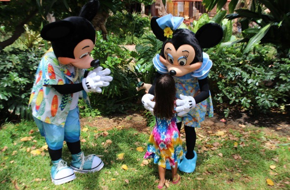 A little girl embraces Mickey and Minnie characters at Aulani, A Disney Resort & Spa