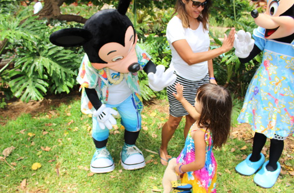 A mother and daughter give high fives to Mickey and Minnie characters