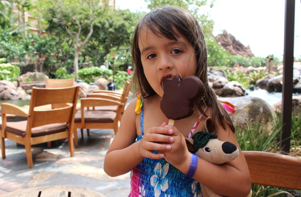 A little girl eats a Mickey Mouse ice-cream outside at the resort