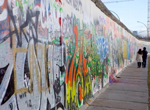 couple walk along berlin wall at east side gallery