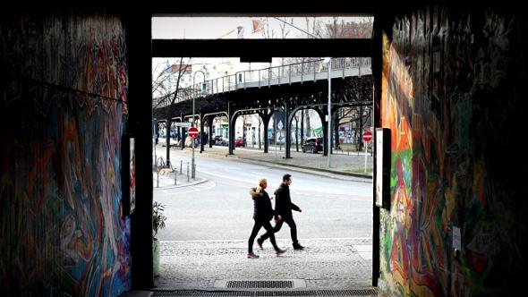 couple walking on berlin street looking from graffiti alley