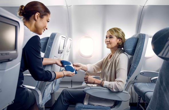 A Finnair flight attendant hands a passenger a Marimekko print amenity kit