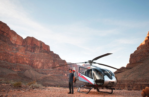 A man stands outside a helicopter that has landed on the floor of the Grand Canyon
