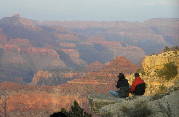A male and female tourist look at the topography of Grand Canyon National Park from a ledge