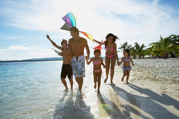 Family running on beach at sunset