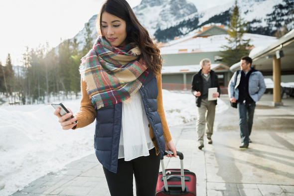 Woman looking at phone towing suitcase in the alps.