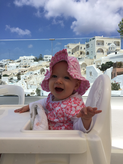 A baby smiles while sitting in a highchair against a backdrop of the whitewashed buildings of Santorini