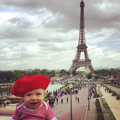 A baby in a red beret poses with the famous Eiffel Tower in the distance