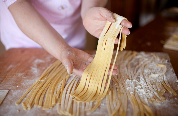 A woman holds some fresh pasta in her hands