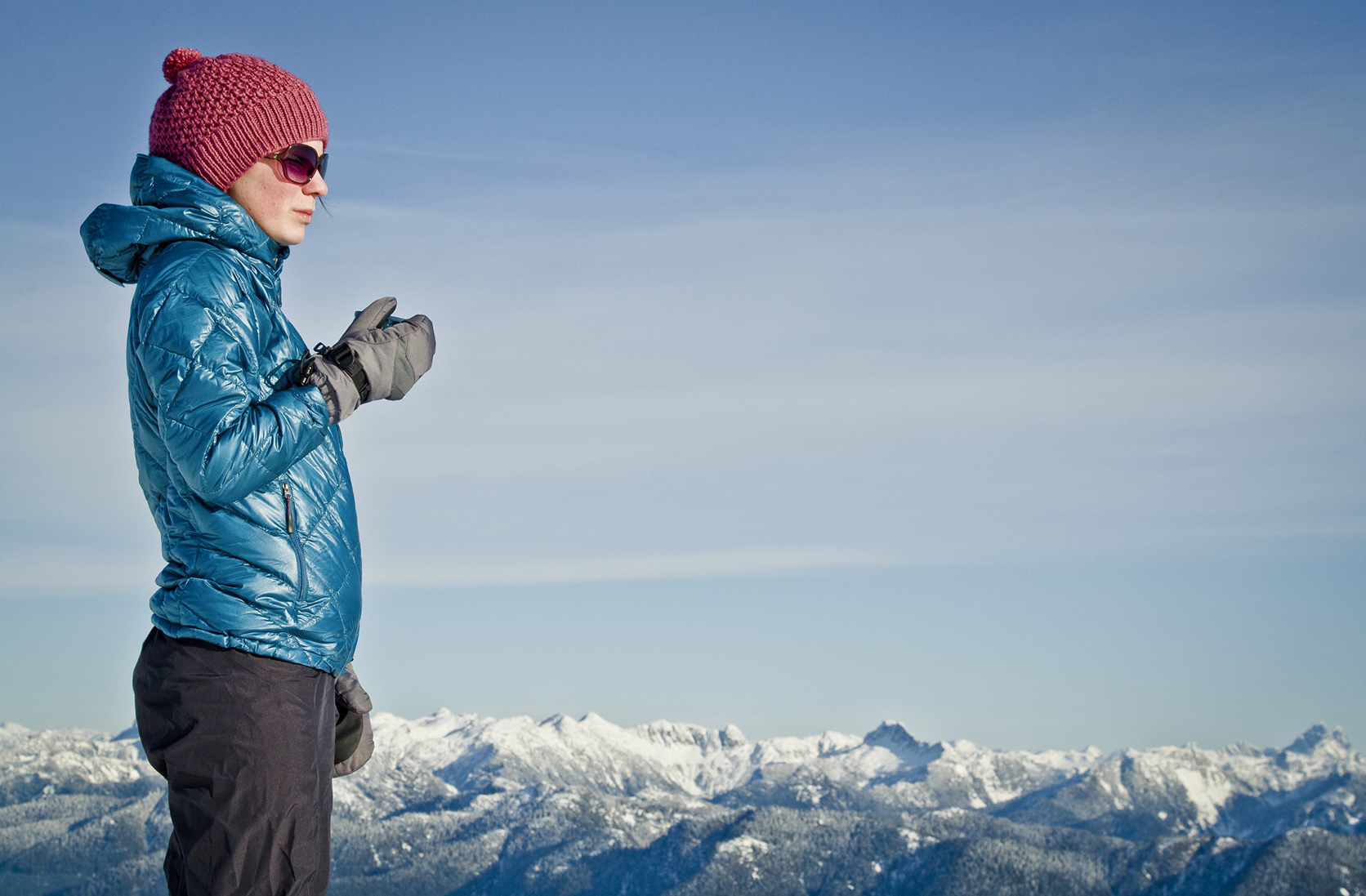 A female snowboarder enjoys a hot drink on Mount Seymour