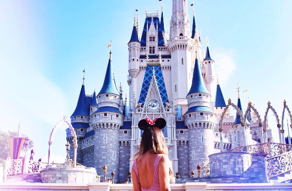 A female stands in front of Cinderella's Castle at Walt Disney World in Orlando, Florida