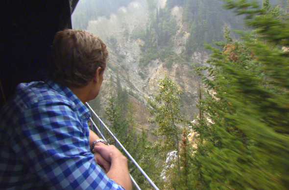 TV host Chris Brown looks at the Canadian Rockies through the window of the Rocky Mountaineer
