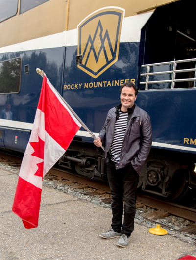TV chef Miguel Maestre waves the Canadian flag outside the Rocky Mountaineer train carriage