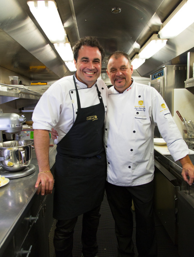 TV chef Miguel Maestre and Rocky Mountaineer Executive Chef Jean Pierre Guerin stand in the onboard kitchen of the Rocky Mountaineer train