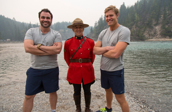 TV hosts Chris Brown and Miguel Maestre pose with a Canadian Mountie outdoors in Canada