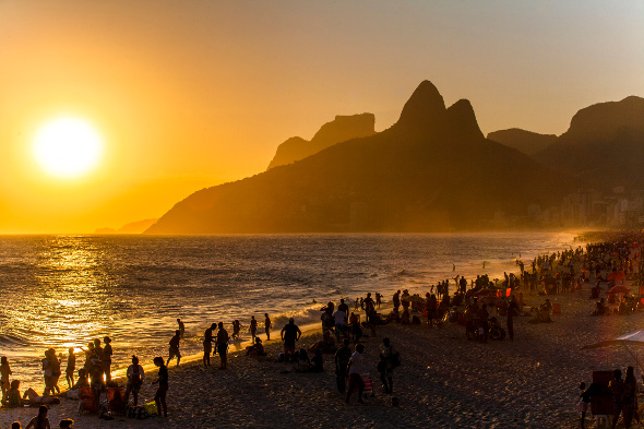 sun set over Ipanema beach packed with bathers