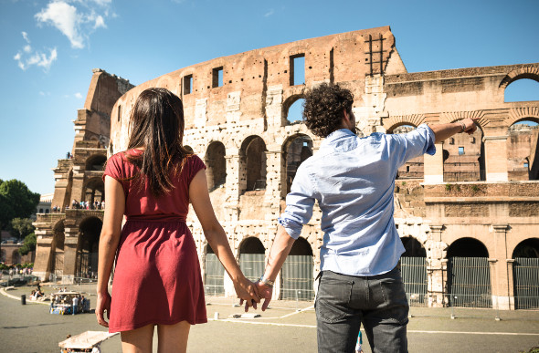 A young couple stands in front looking at the Colosseum in Rome