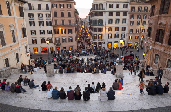 A stunning view of Piazza di Spagna in Rome from the Spanish Steps at dusk with lots of people in the area