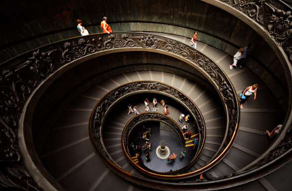 People wander down a spiral staircase in the Vatican Museum in Vatican City