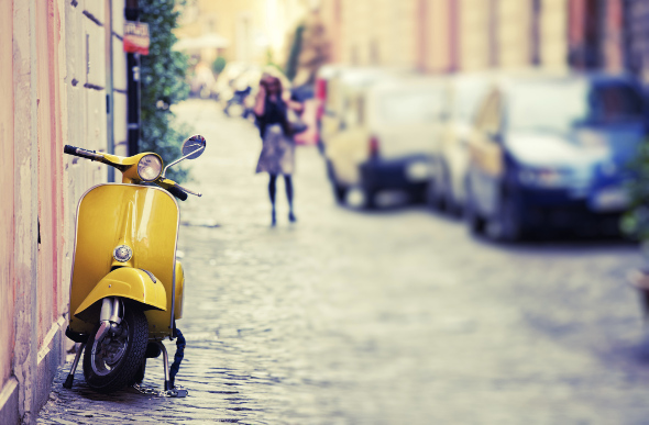 A vintage yellow Vespa is parked on a charming street in Rome