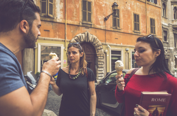 Three young tourists sample different gelato flavours in a Rome street