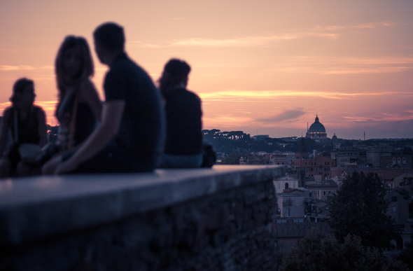 People watching the sun set from a bridge in Rome