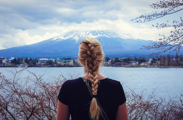 A young blonde women looks at Mount Fuji in the distance with her back to the camera