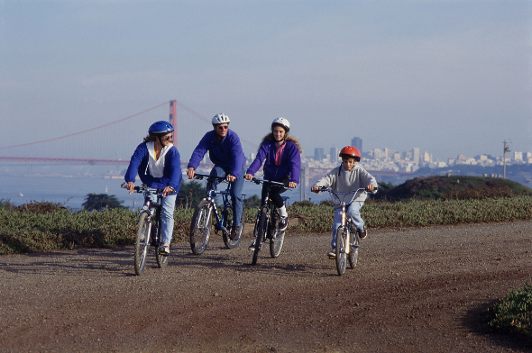 family riding bikes with golden gate bridge and san francisco in background