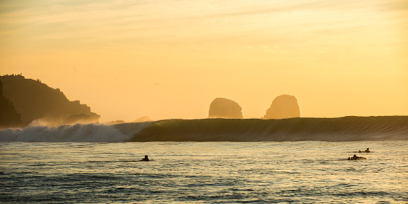 surfers paddling out at pichilemu chile at dusk