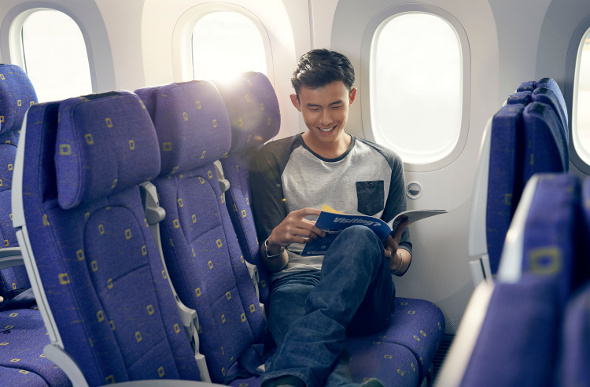 A passenger stretches his legs across the airline seats on a Scoot plane