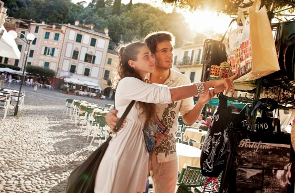 Young couple on vacation in Portofino shopping for souvenirs.