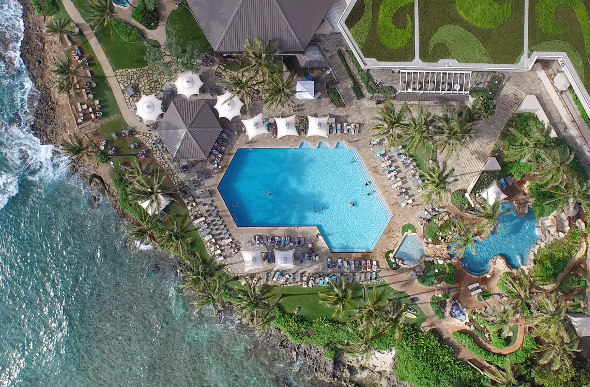 An aerial shot of the ground of Turtle Bay Resort on the North Shore of Oahu shows the pool areas and the ocean