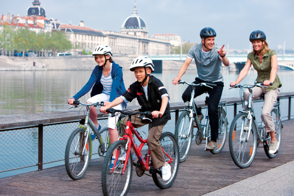 Family cycling along Danube river in Budapest