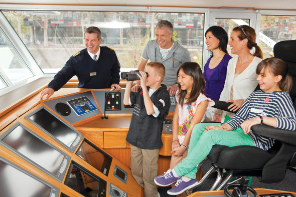Family on bridge on river cruise with captain