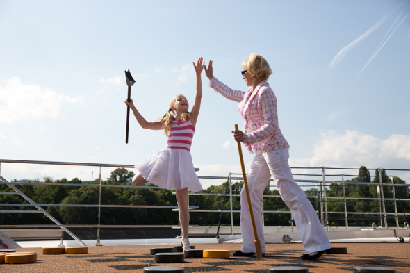 Mother playing shuffle board with her daughter on the deck of a cruise ship