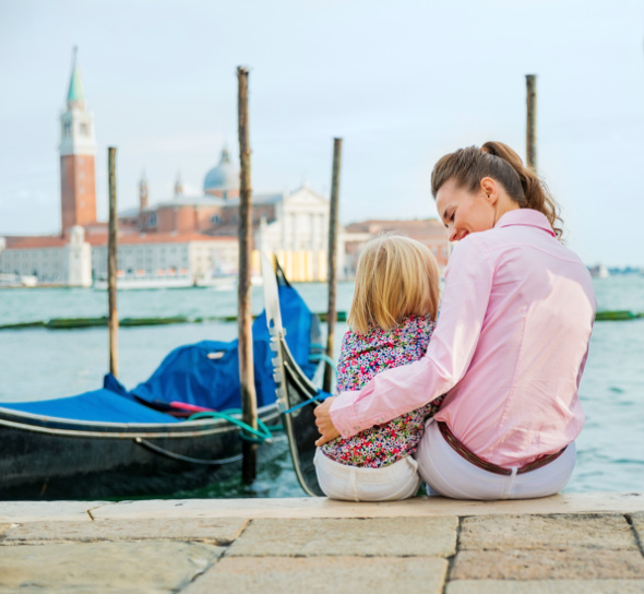 Mother hugging daughter at waters edge in venice
