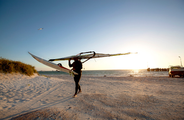 A windsurfer walks along the beach at Lancelin in Western Australia.