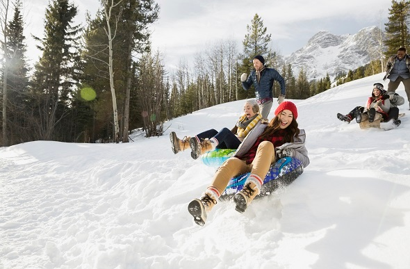 Friends sliding down a snowy mountain in blow up tubes.