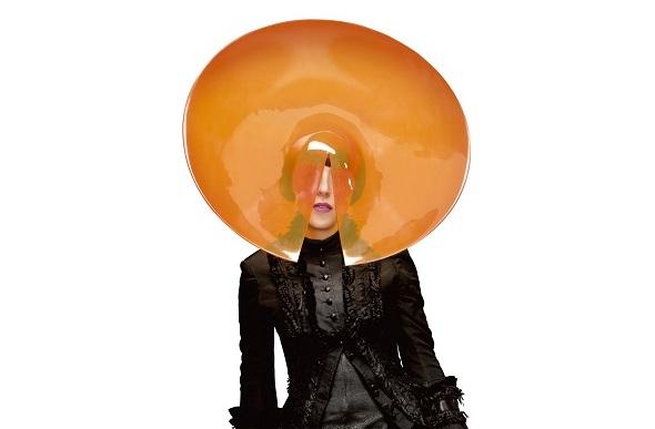 Stylist Isabella Blow wears an orange acrylic disk hat.