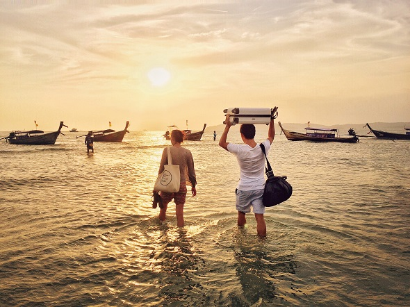 Young couple at Ao Nang beach in Krabi province walking into the ocean to long tail boats during low tide and holding their bags over their heads.