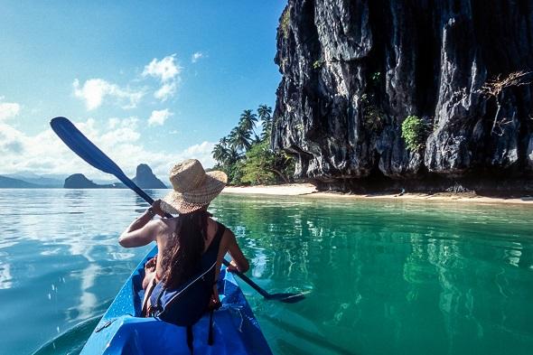 A woman sea kayaking in Bacuit Bay,  Palawan, El Nido, The Philippines.
