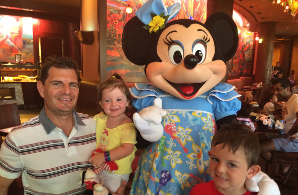 A family posing for photo with Minnie at Aulani, A Disney Resort & Spa