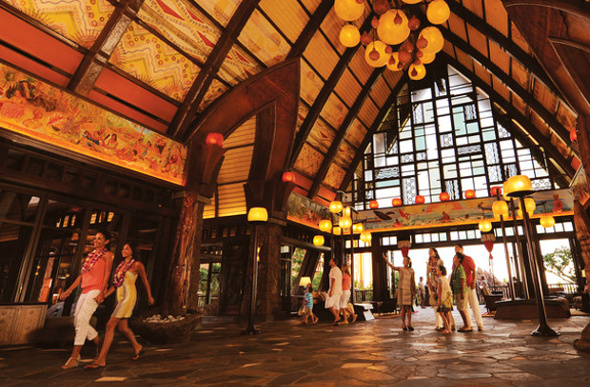 A family being greeted inside the Hawaiian-style lobby of Aulani, A Disney Resort & Spa